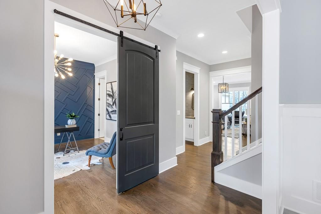 A foyer space in a new house with designer lighting on the ceilings above.