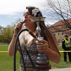 A student uses a water pipe to smoke marijuana outside the police barrier on the Norlin Quad at the University of Colorado in Boulder, Colo., on Friday, April 20, 2012. Police blocked off the quad to prevent a 420 marijuana smoke out.