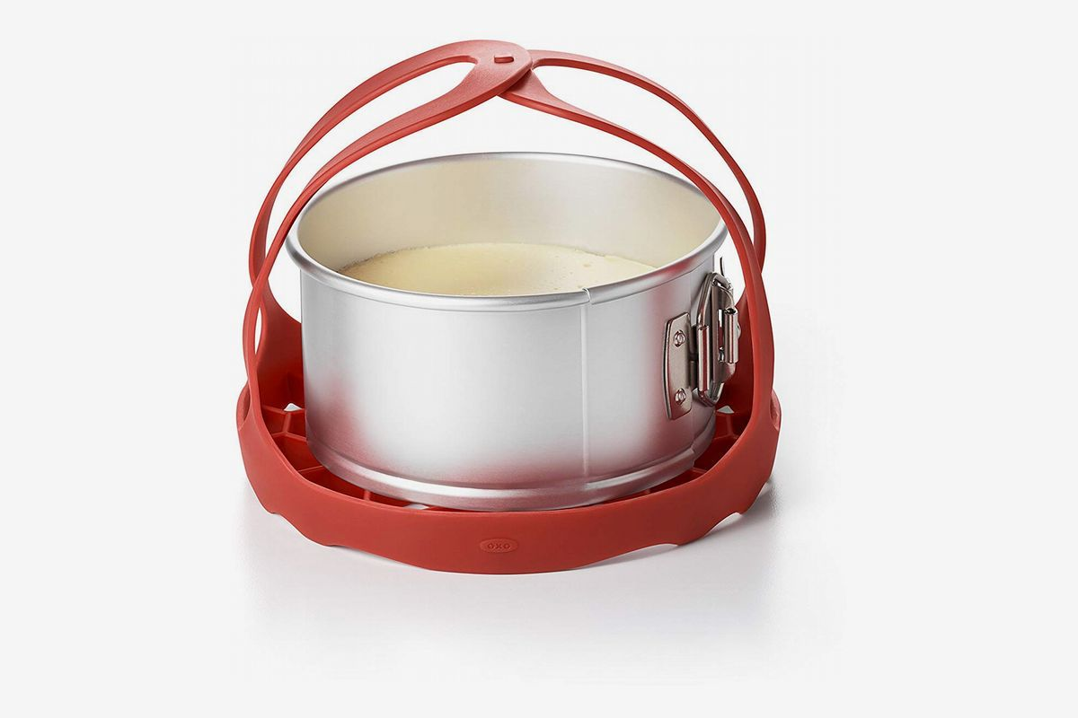 A red silicone sling tied around a cake pan