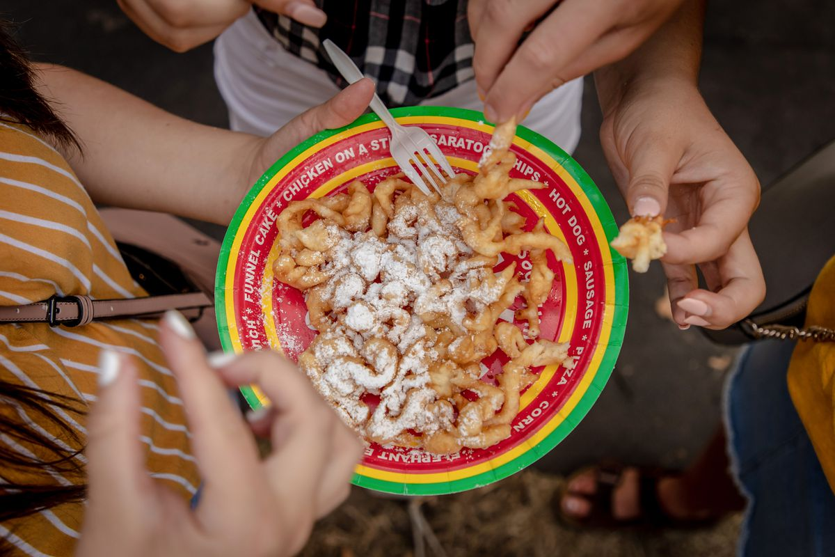 People pick at a powdered-sugar-coated funnel cake on a plate.