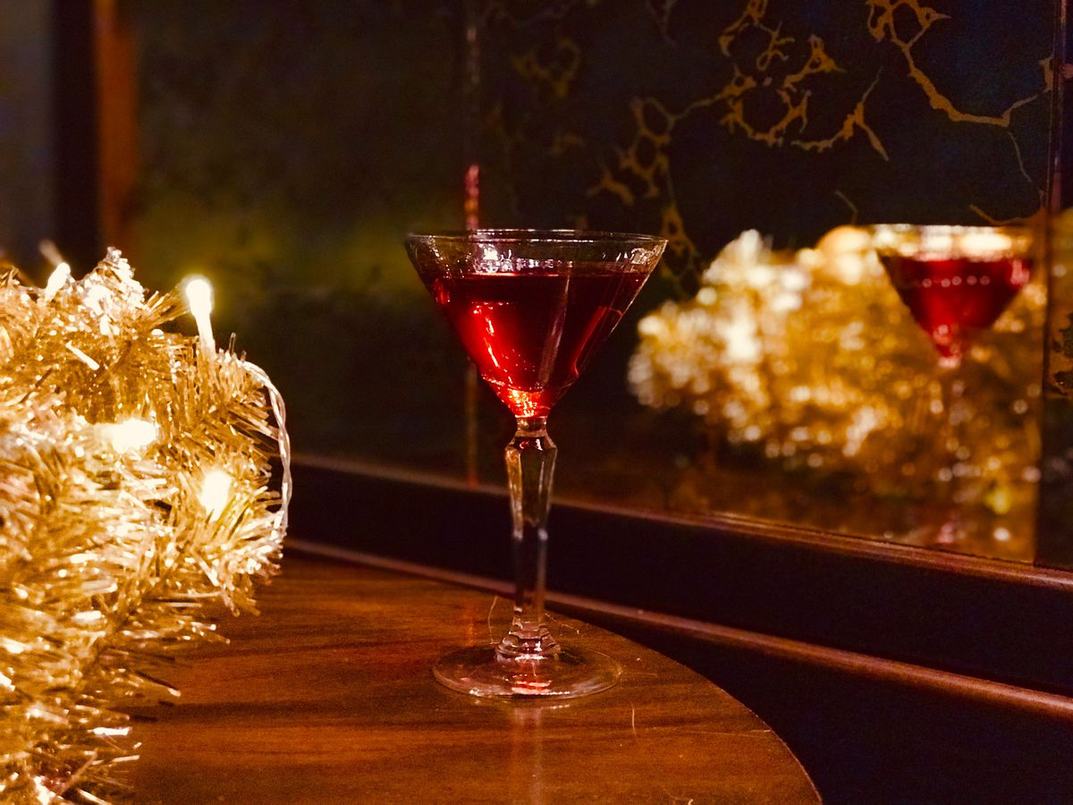 A dark red cocktail in a martini glass with shimmering lights around it.