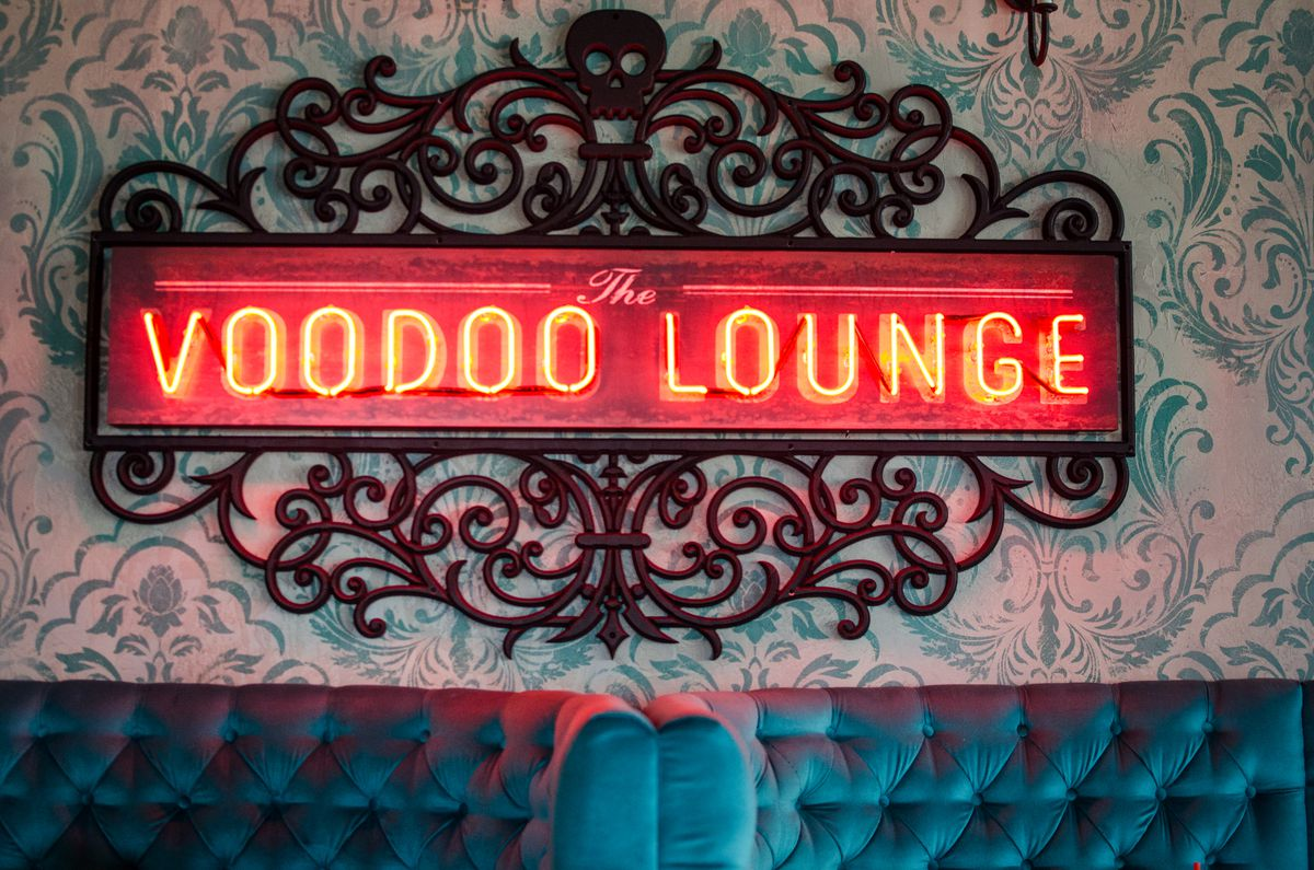"""A red neon sign reads """"the Voodoo Lounge"""" in capital letters. It's surrounded by curved black steelwork with a skull at the top. It's on a white wall with a light blue flowery pattern, and plus teal restaurant booths are visible at the bottom of the photo."""
