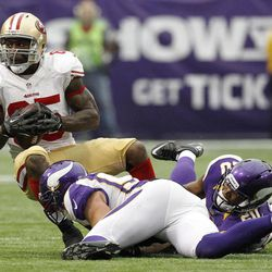 San Francisco 49ers tight end Vernon Davis, top, is tackled by Minnesota Vikings outside linebacker Chad Greenway and cornerback Chris Cook, right, after making a reception during the second half of an NFL football game Sunday, Sept. 23, 2012, in Minneapolis. The Vikings won 24-13.