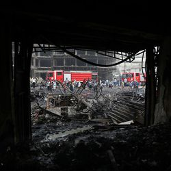 Iraqi security forces and civilians gather at the site after a car bomb hit Karada, a busy shopping district in the center of Baghdad, Iraq, Sunday, July 3, 2016. Dozens of people have been killed and more than 100 wounded in two separate bomb attacks in the Iraqi capital Sunday morning, Iraqi officials said.