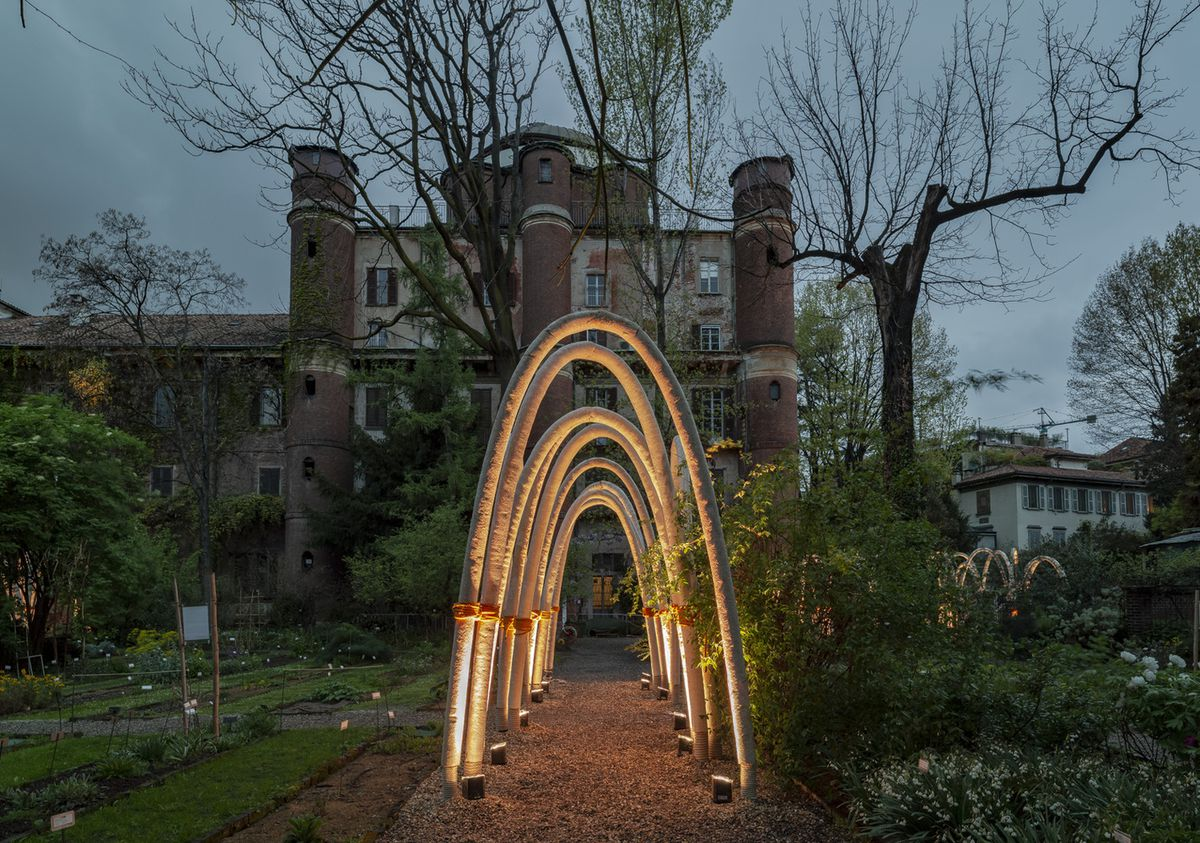 Arches in front of large brick house