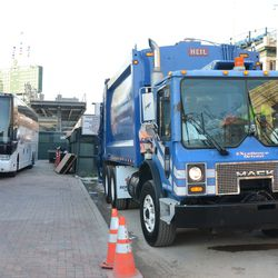 5:37 p.m. Garbage truck parked near the visiting team bus -