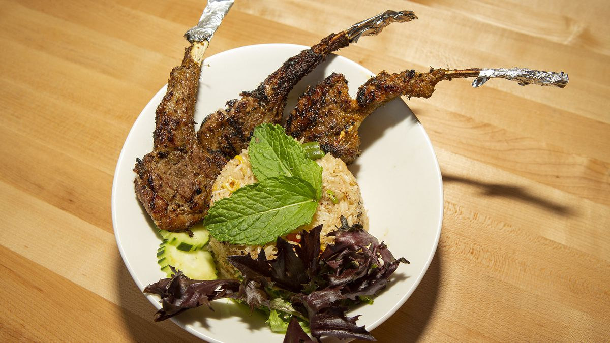 Lamb chops and rice on a dish.