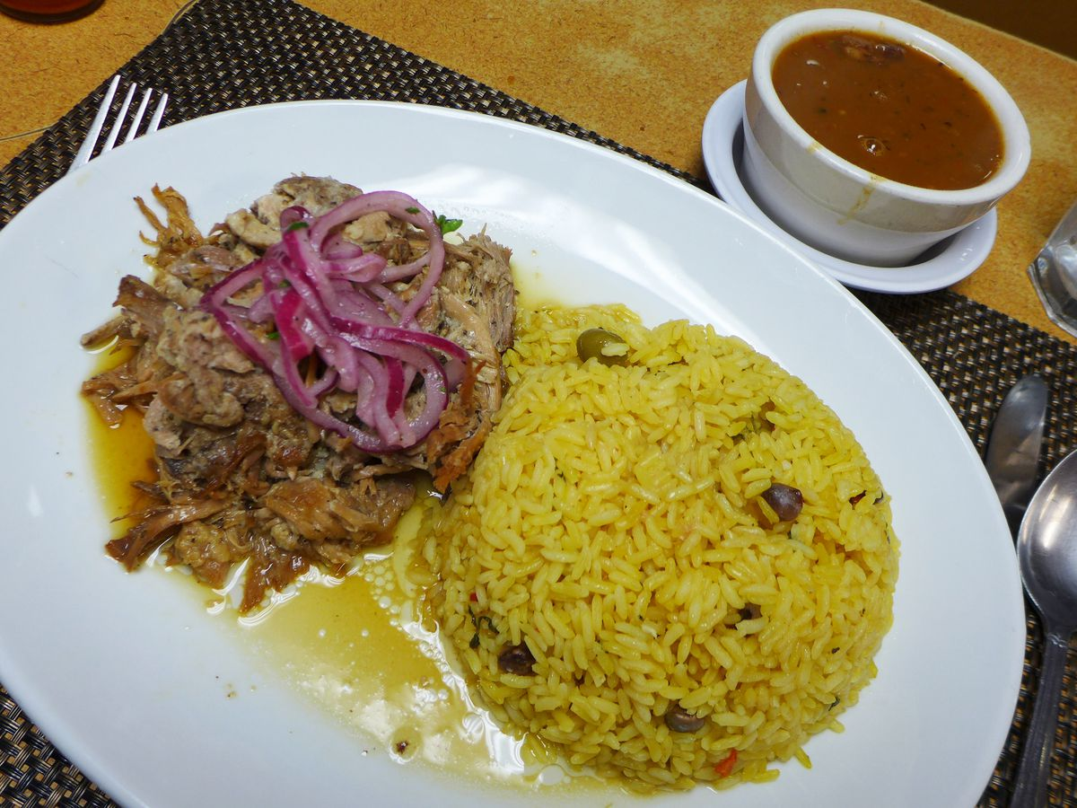 Shredded roast pork with a dome of yellow rice on the side.