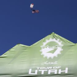 A paraglider carries an American flag to the start line before Stage 3 of the Tour of Utah on Antelope Island on Thursday, Aug. 15, 2019.