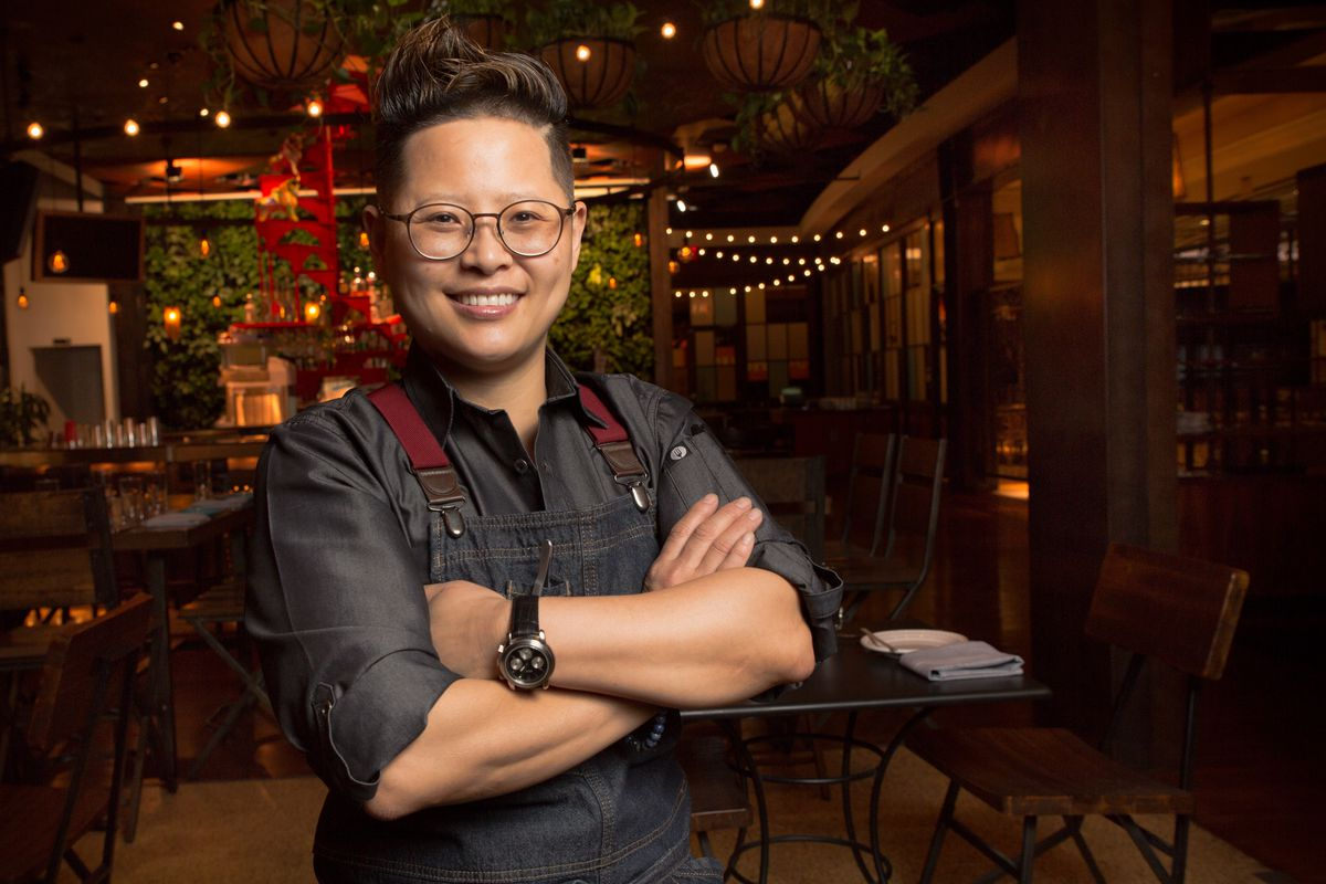 A woman chef stands in front of her restaurant with her arms crossed