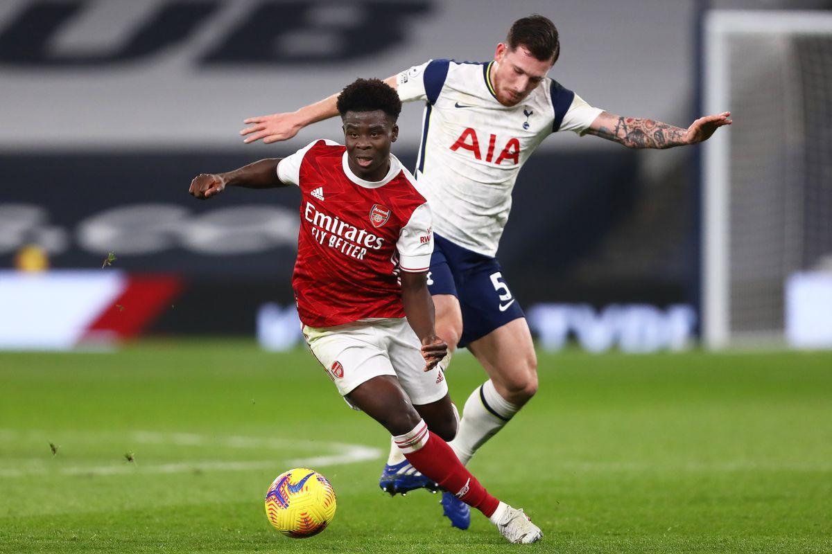 Bukayo Saka of Arsenal and Pierre-Emile Hojbjerg of...
