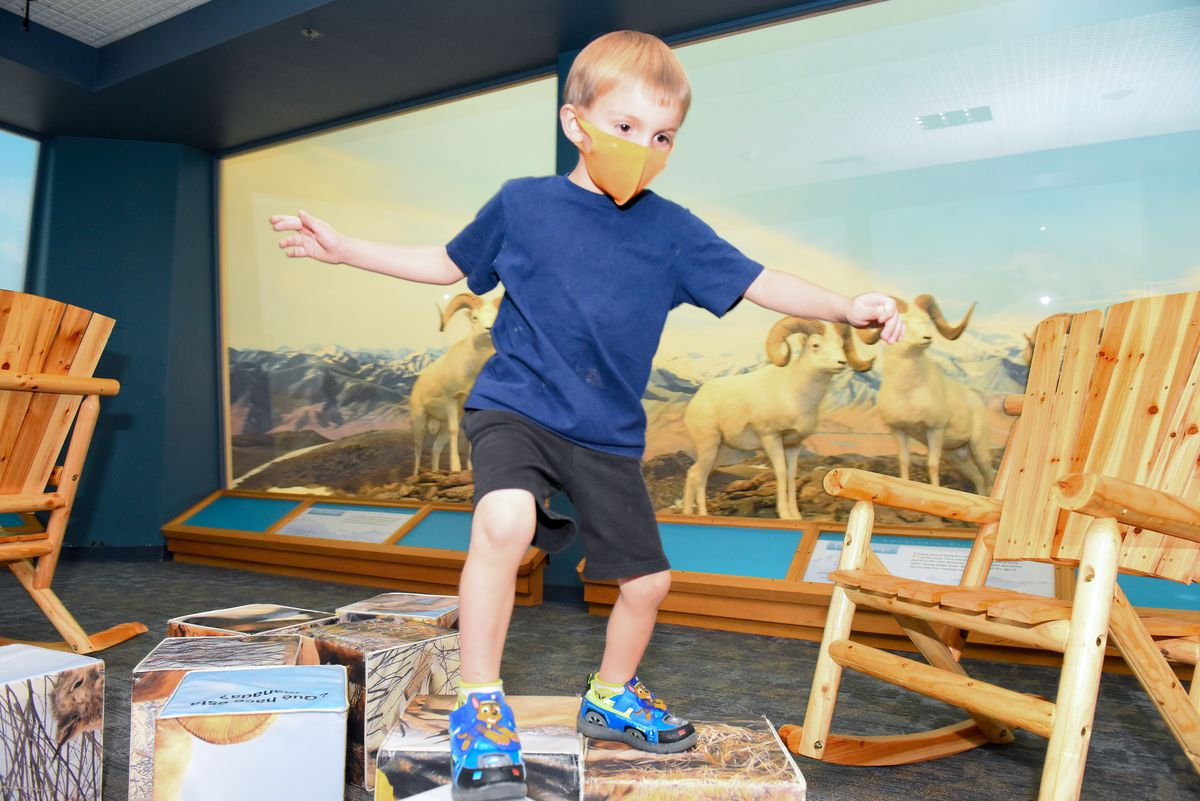 A young child wearing an orange face mask plays at the Denver Museum of Nature & Science