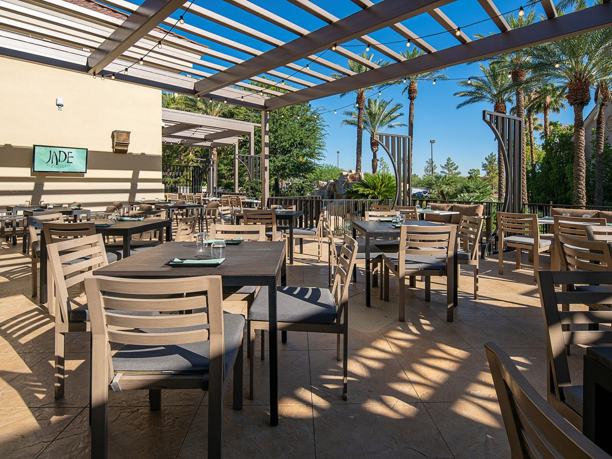A patio with wooden chairs and tables.