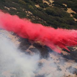 A small SEAT plane drops retardant near the fire line as it burns near the mouth of Weber Canyon on Tuesday, Sept. 5, 2017.