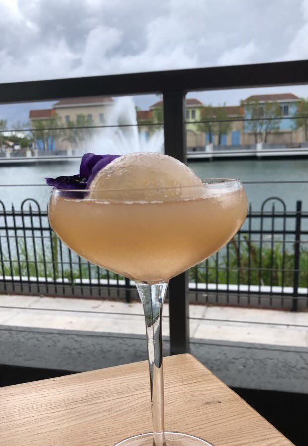 A light orange cocktail in a coupe glass with a large circular ice cube and a purple flower, on an outdoor table in front of a fountain