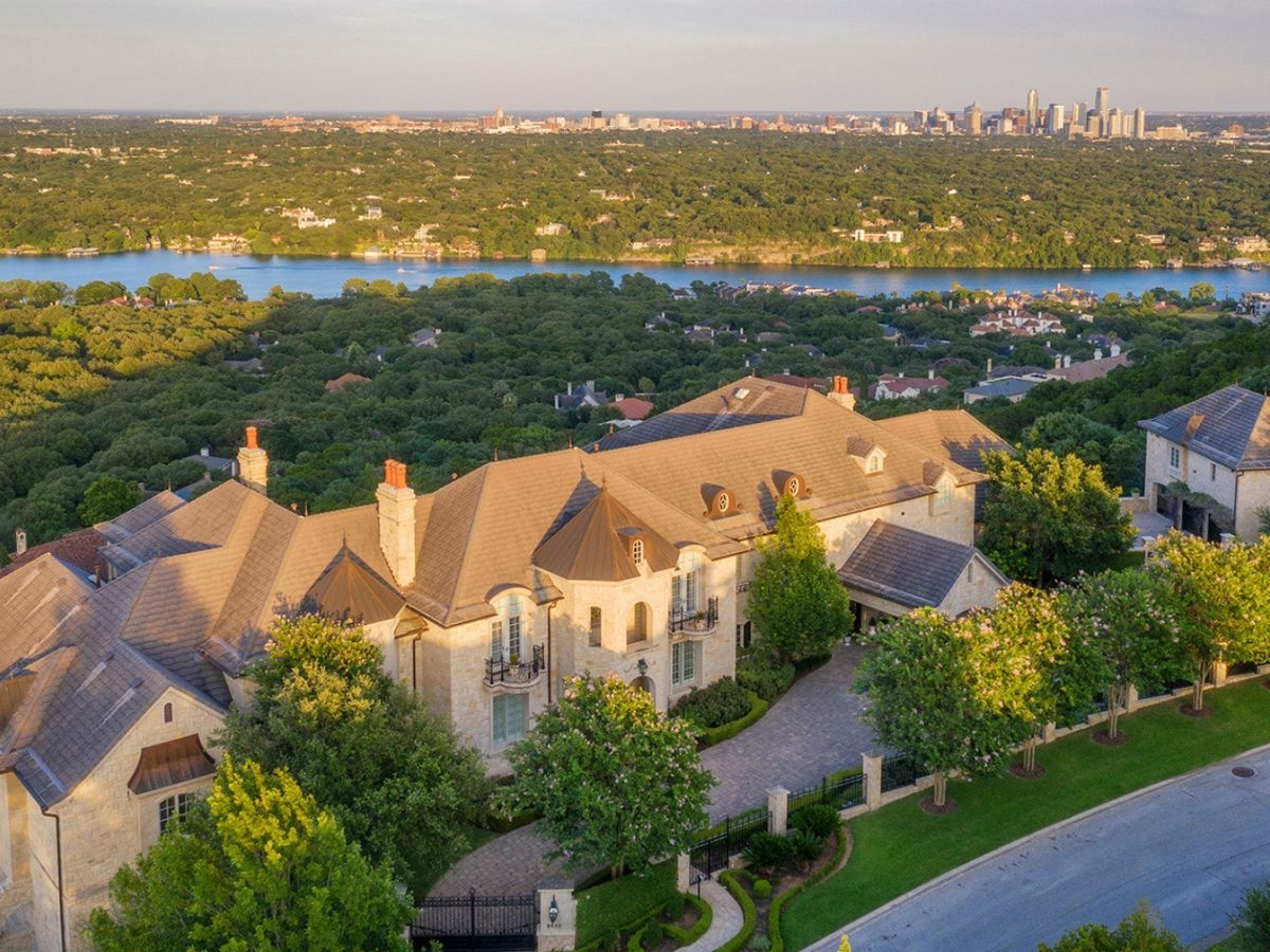 A castle-like McMansion photographed from front and above. There's a river in the background and a large group of tall buildings in the distance, which is downtown Austin.