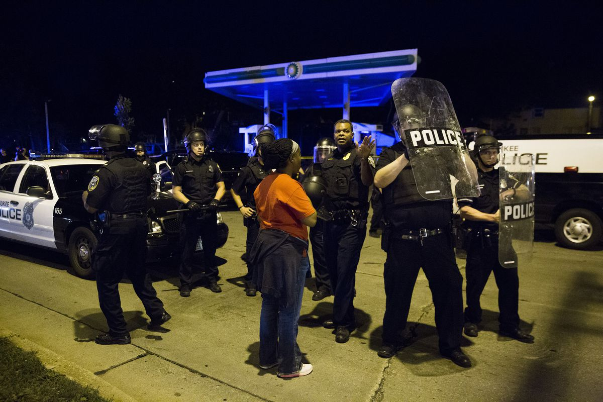 A civilian speaks with police during late night protests over the fatal shooting of Sylville Smith, on August 14, 2016.