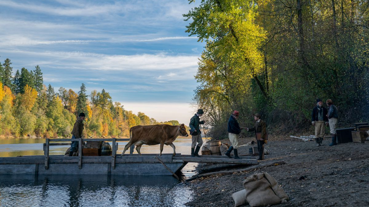 A cow walks off of a barge onto the beaches of the river in 'First Cow'