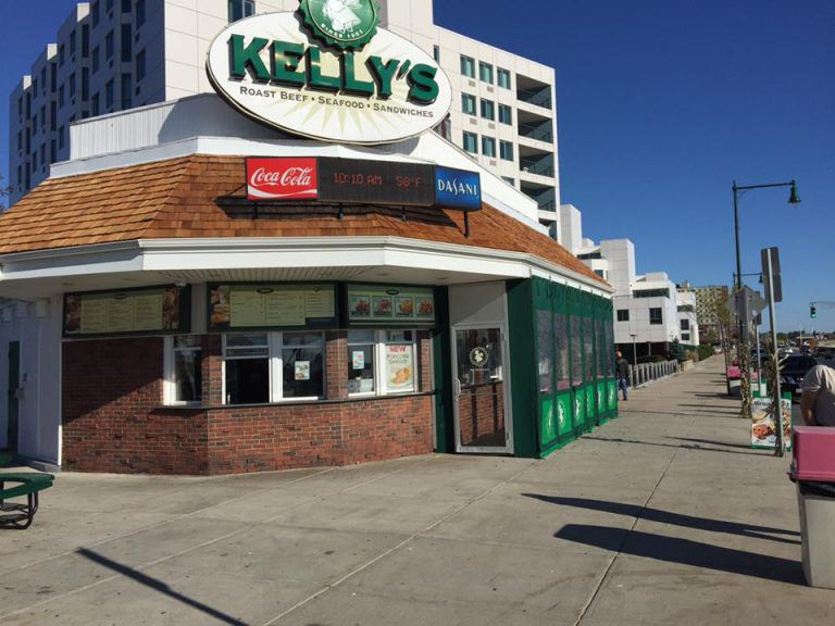 Brick-lined takeout restaurant exterior with large sign that says Kelly's