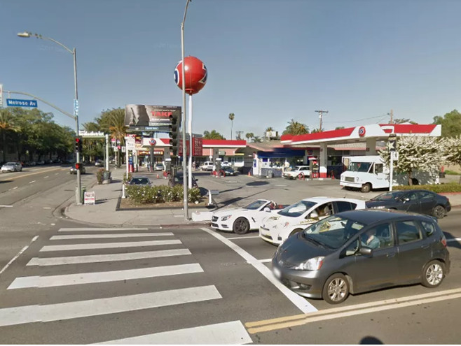A gas station. There is a city intersection in front of the gas station with cars stopped at a traffic light.