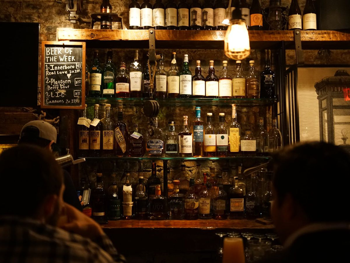 A brick wall has shelves with lots of liquor bottles, plus a sign displaying the beer of the week in chalk