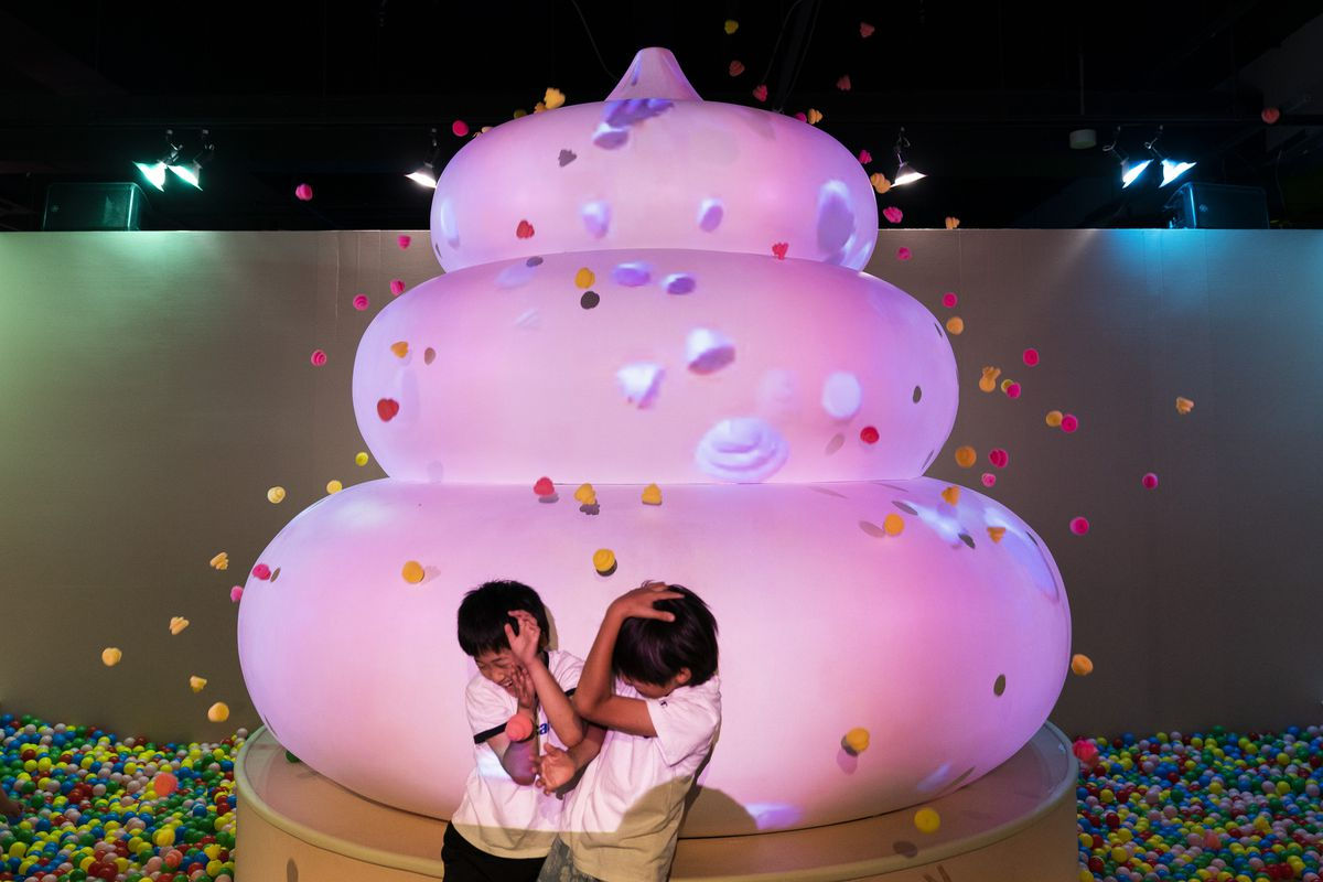 In this Tuesday, June 18, 2019, photo, two boys jokingly take cover as small toy poops gush from a giant poop-shaped inflatable at the Unko Museum in Yokohama, south of Tokyo.