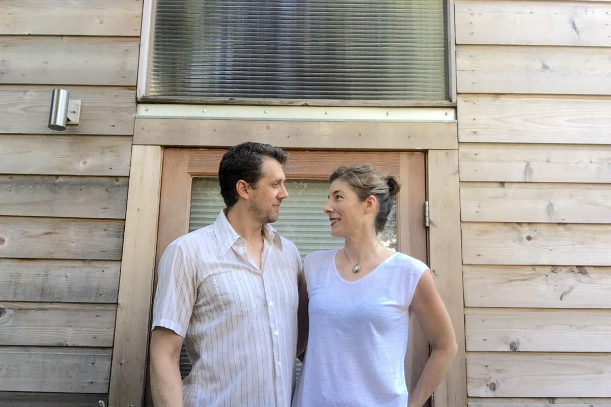 A man on the left and a woman on the right looking at each other lovingly in front of a wood-shingled house