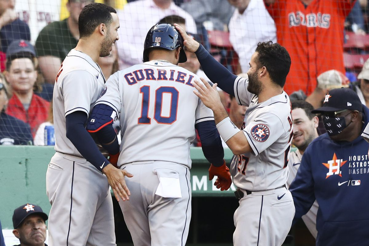 Yuli Gurriel #10 high fives Carlos Correa #1 of the Houston Astros as he returns to the dugout after hitting a solo home run in the second inning of a game against the Boston Red Sox at Fenway Park on June 10, 2021 in Boston, Massachusetts.