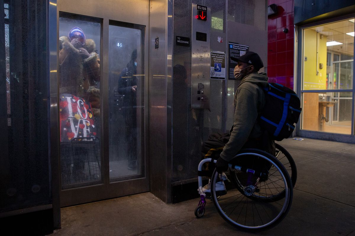 Saheed Adebayo Aare waits for an elevator in East Harlem during the start of his three-hour commute from a Wards Island shelter to a New Jersey Amazon fulfillment center, Feb. 24, 2021.