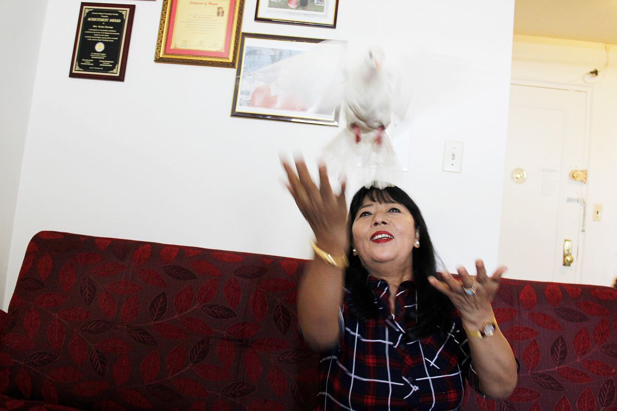 Goma Yonjan with her pet bird, Pari, at her Woodside apartment, Sept. 2, 2021.