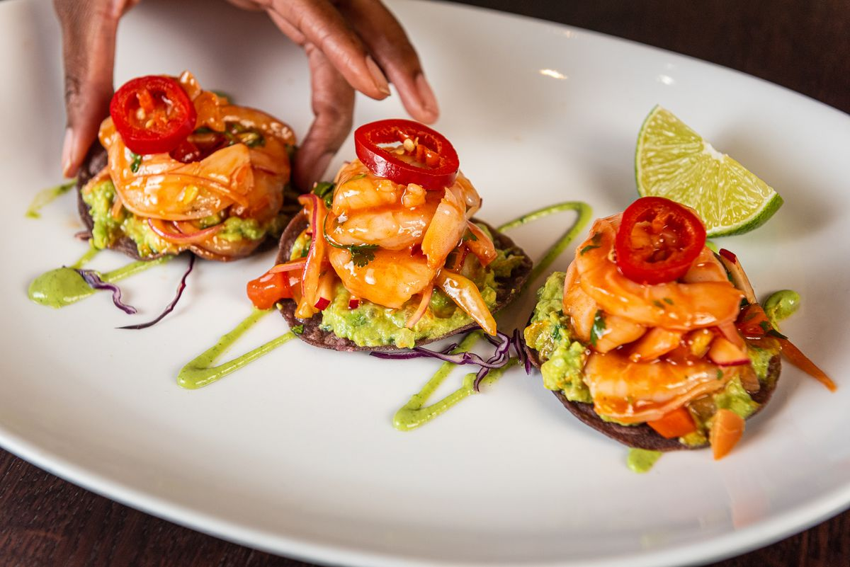 Three Yucatan shrimp tostadas at Anafre are built on blue tortillas with a base of green guacamole on a white plate.