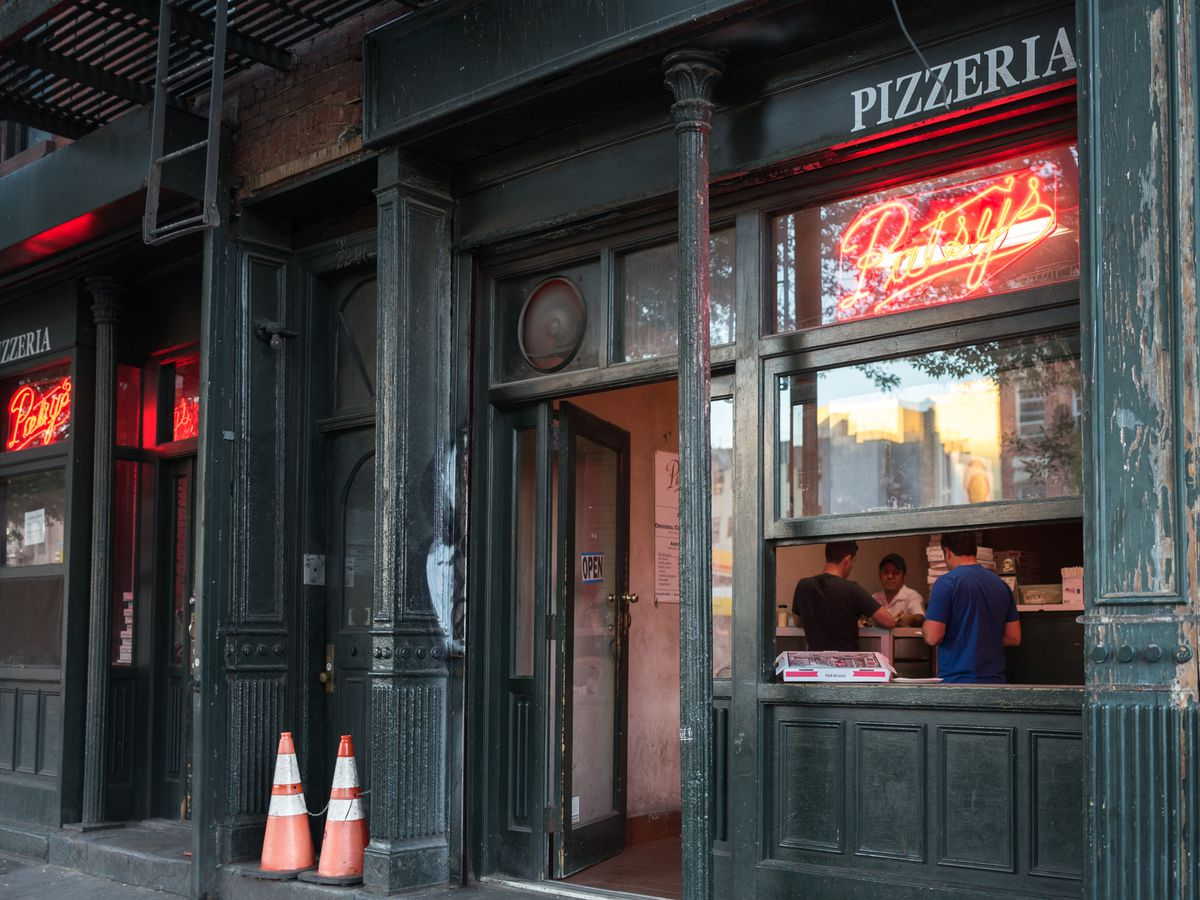 """Patsy's in East Harlem has a dark exterior with a red """"Patsy's"""" neon sign"""