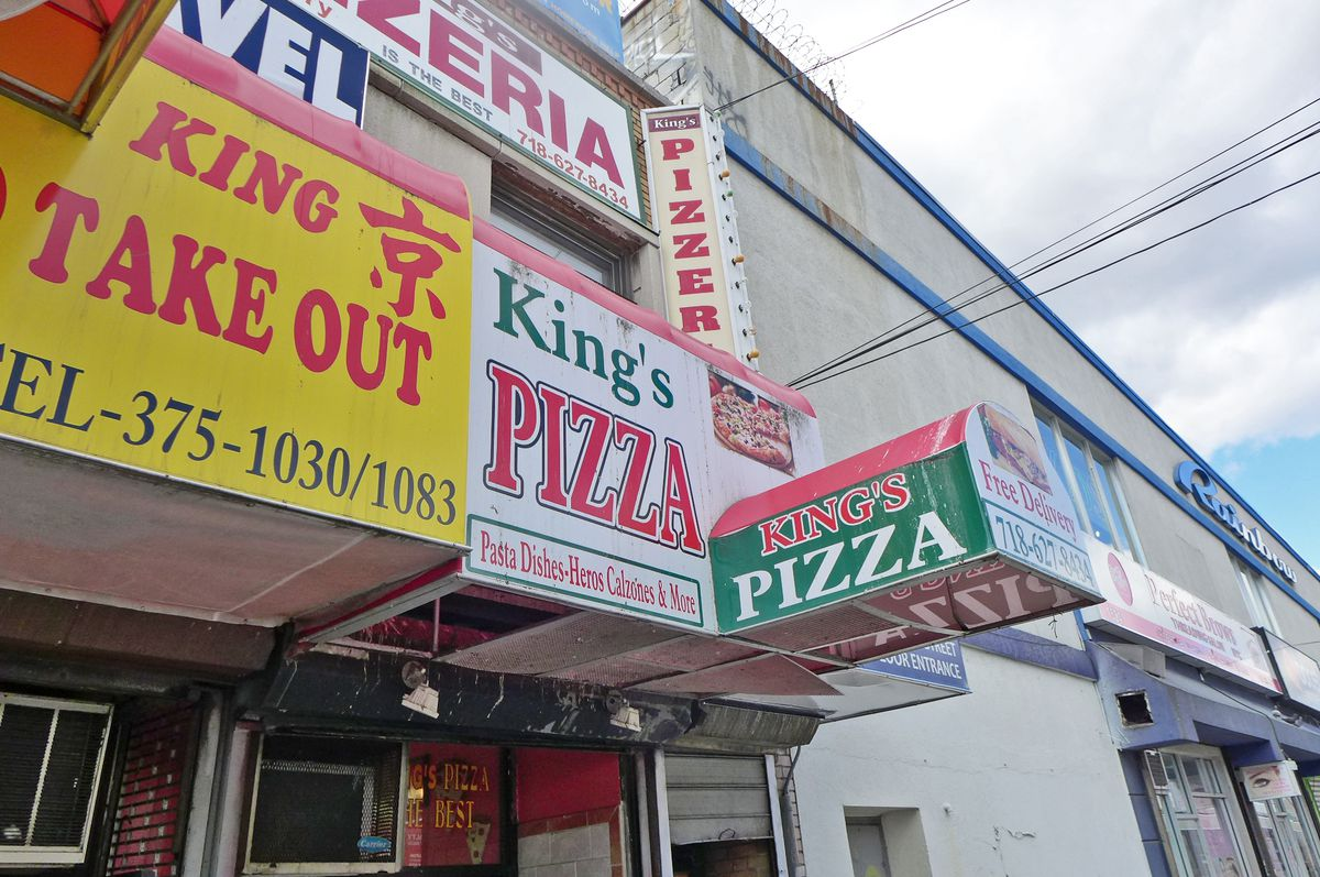 Several facades and signs jumbled up with King's Pizza in the middle