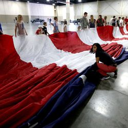 People help unfurl a giant American flag at the South Towne Expo Center in Sandy on Wednesday, May 31, 2017. The flag, which measures 78 feet by 125 feet, will fly between the two peaks at Grove Canyon in Pleasant Grove on the morning of July 4th. The organization Follow the Flag believes it will be the largest American flag ever flown.