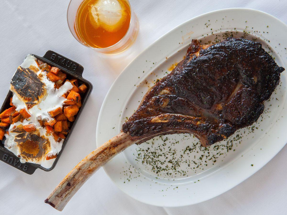 A tomahawk steak accompanied by a side.