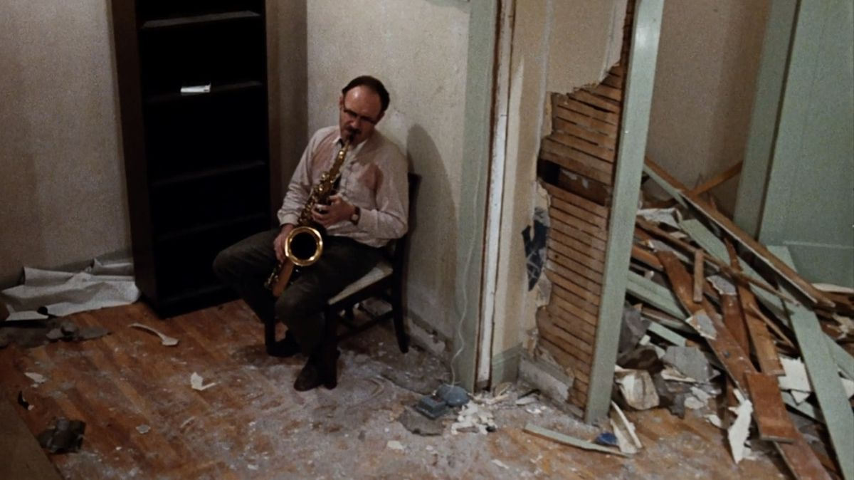 Gene Hackman as Harry Caul forlornly playing the saxophone in a ransacked apartment in The Conversation