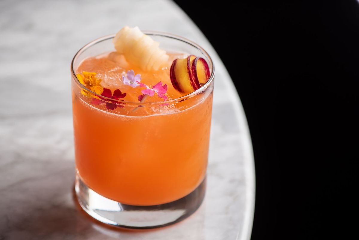 An orange cocktail filled with a variety of fruit garnishes.