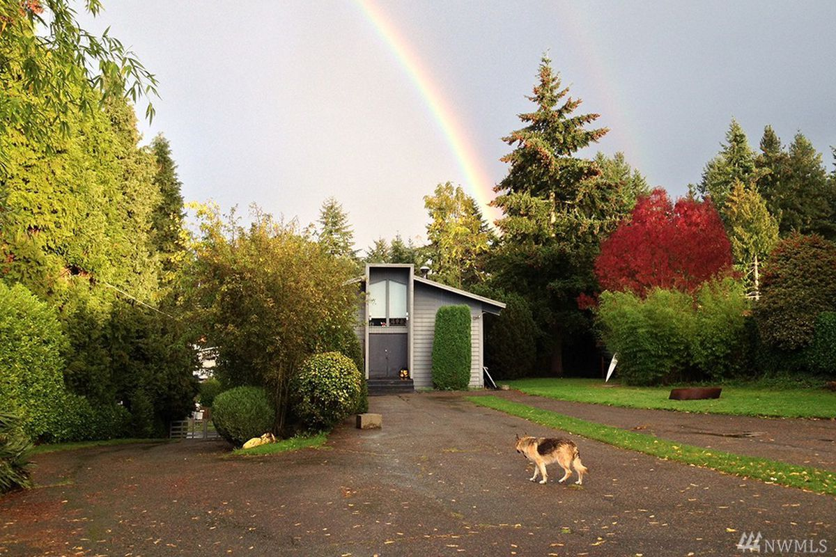 The front of a church with a dog running in a yard far ahead in the foreground. A double rainbow is in the sky above.