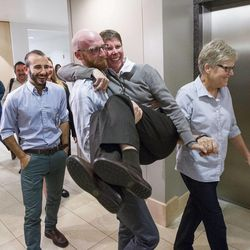 Derek Kitchen picks up Laurie Wood as Amendment 3 case plaintiffs leave a press conference Monday, Oct. 6, 2014, in the office of attorney Peggy Tomsic in Salt Lake City, after the U.S. Supreme Court refused to hear appeals on lower court rulings that allowed same-sex marriages, making them legal in Utah and other states.