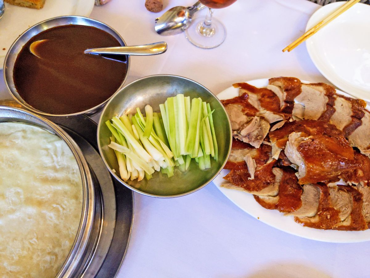 In separate serving vessels, sliced duck, cucumbers and scallions, steamed pancakes, and dark red hoisin sauce.