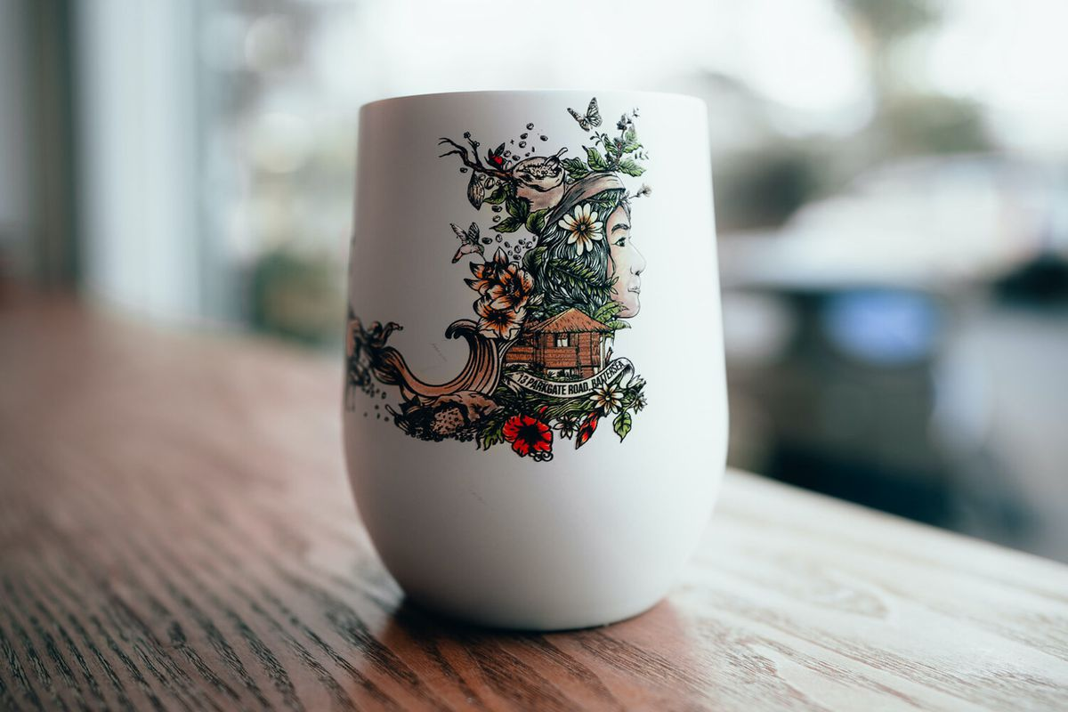 A coffee cup hand-illustrated with a Filipino coffee farm