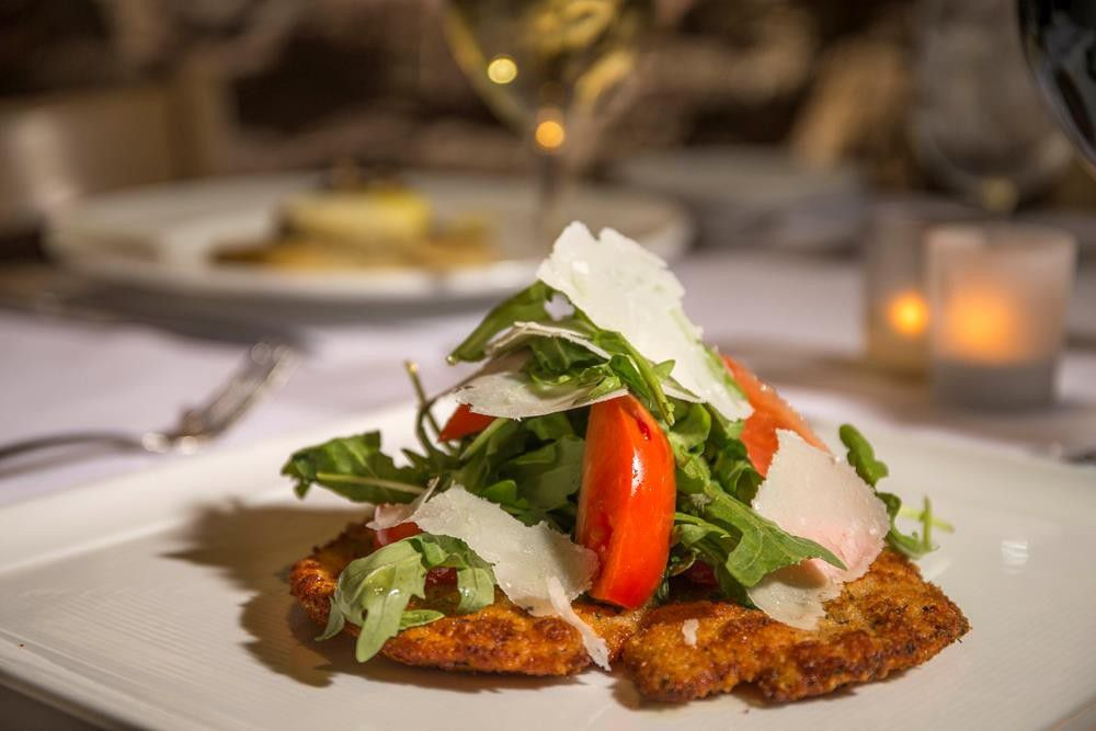A salad of lettuce, tomato, cheese on top of breaded chicken, with a set table blurred behind