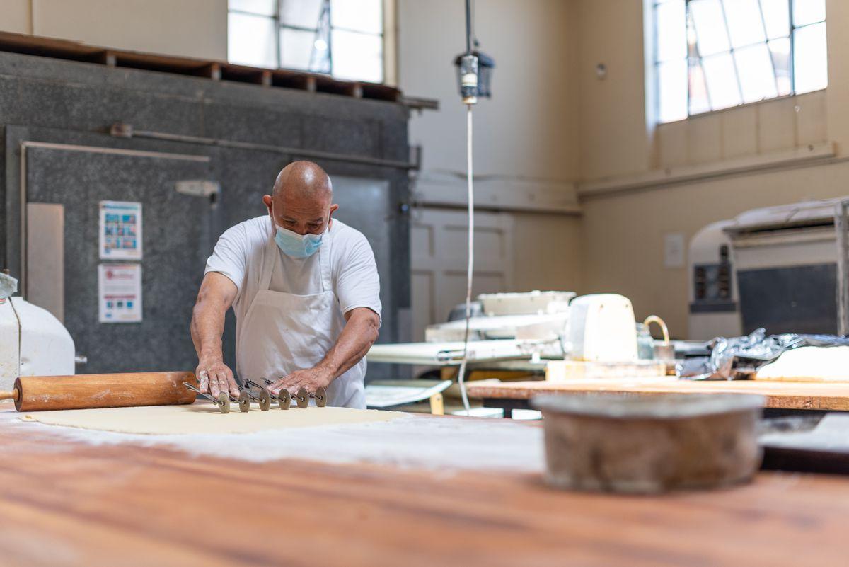 Một công nhân lăn ra và cắt một tấm bột bên trong một tiệm bánh cũ mờ.