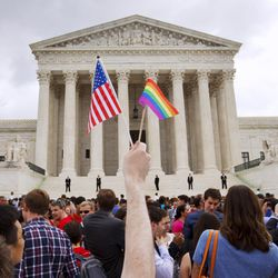 In this Friday June 26, 2015, file photo, a man holds a U.S. and a rainbow flag outside the Supreme Court in Washington after the court legalized gay marriage nationwide. After the decision, religious conservatives are focusing on preserving their right to object. Their concerns are for the thousands of faith-based charities, colleges and hospitals that want to hire, fire, serve and set policy according to their religious beliefs, notably that gay relationships are morally wrong.