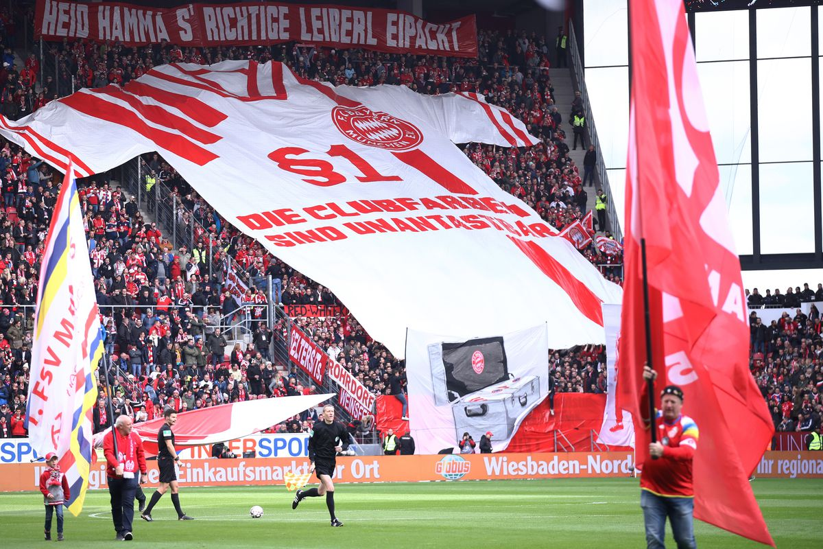 """MAINZ, GERMANY - OCTOBER 27: Fans display a flag in the shape of a shirt prior to the Bundesliga match between 1. FSV Mainz 05 and FC Bayern Muenchen at Opel Arena on October 27, 2018 in Mainz, Germany. The choreo reads, """"§1. Die Clubfarben sind unantastbar,"""" """"§1. The club colors are inviolable,"""" parodying Bayern chairman Karl-Heinz Rummenigge's quotation of article 1 of the German Grundgesetz (constitution) at a notorious press conference in October. The choreo protests Bayern's mint-green away jerseys."""
