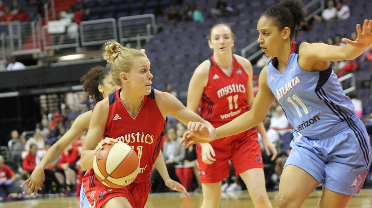 Washington Mystics Jamie Weisner is dribbling the basketball with forward Ally Malott in the background.