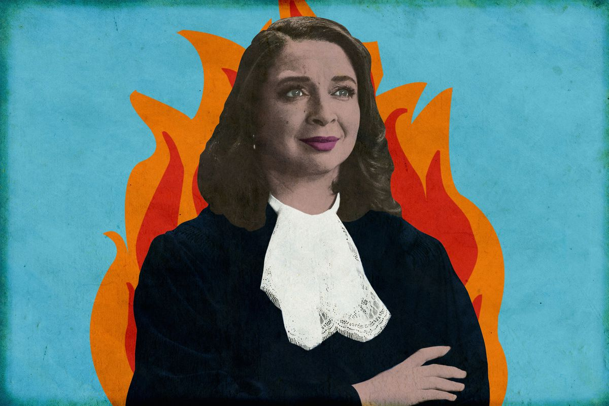 Maya Rudolph as the Judge on 'The Good Place' standing in front of an illustration of a fire