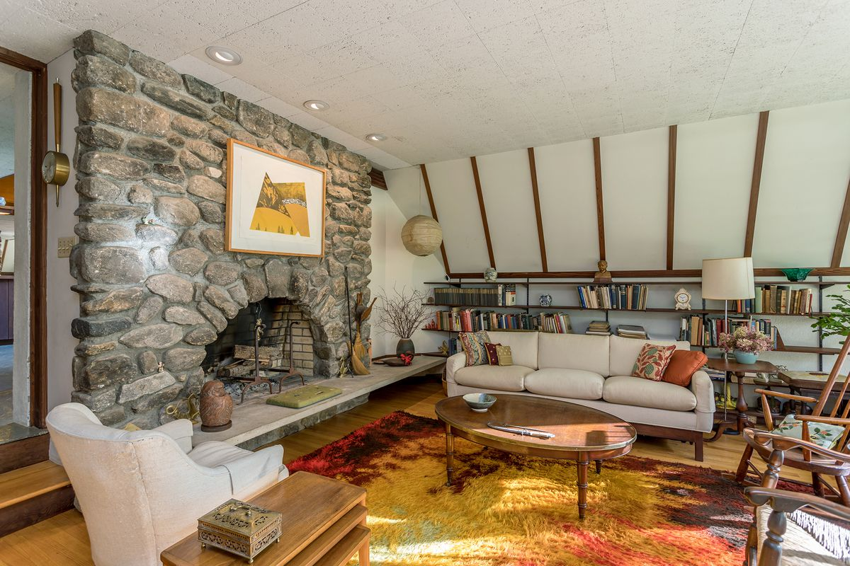A living room with an arched stone fireplace, white couch, seating, and a brightly colored yellow and red rug.