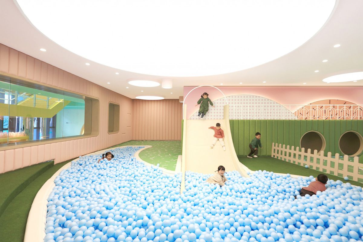 Children riding pale yellow slide into ball pit of light blue balls. The ground is green while the walls are light pink.