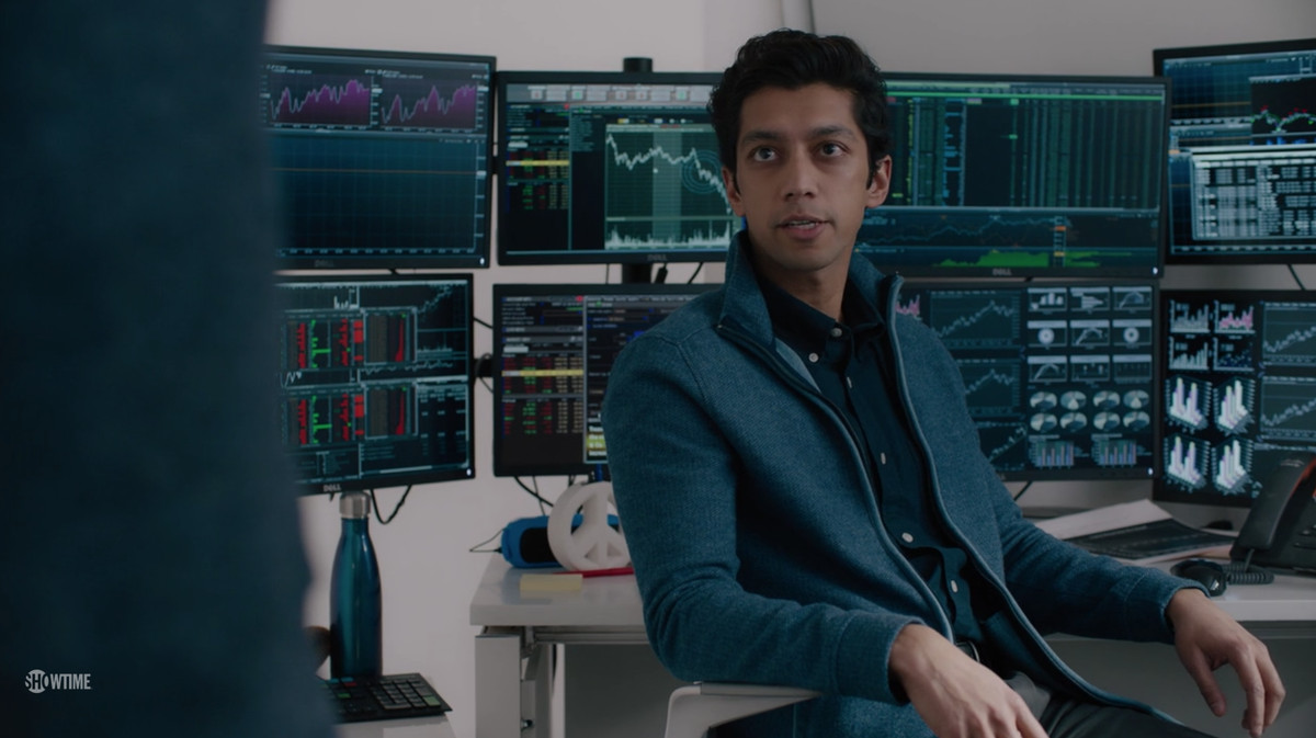 Image of a man sitting in front of many computer monitors with graphs on them